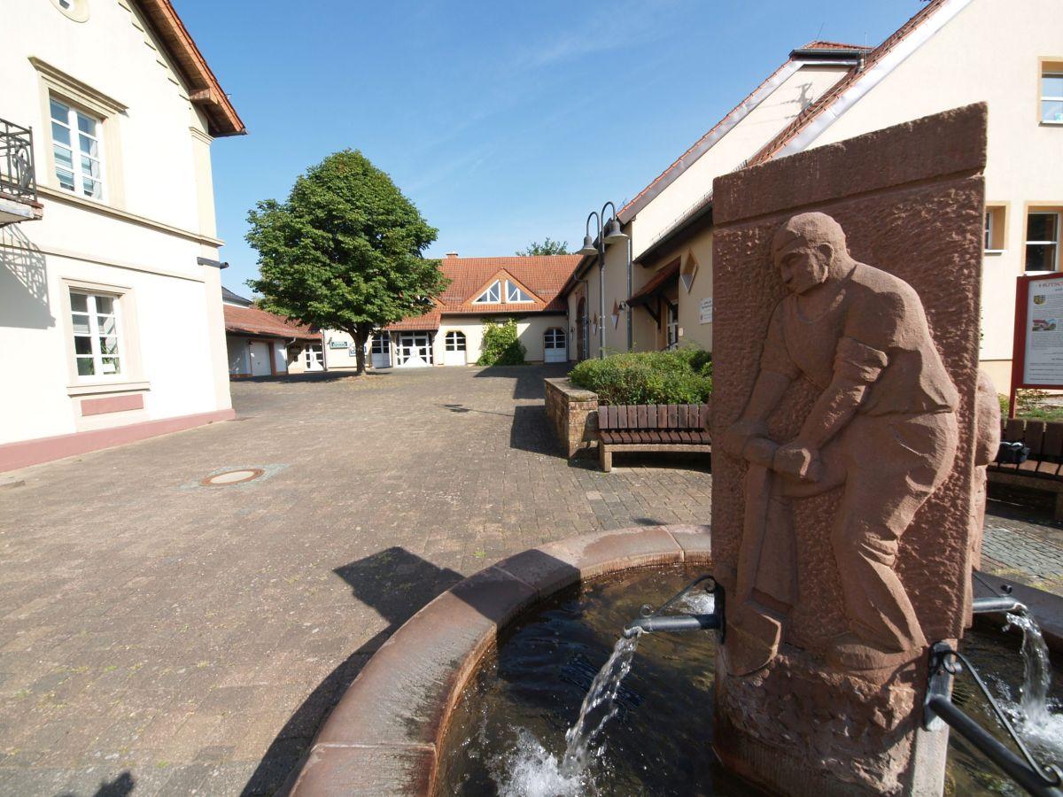 Der Brunnen mit Blick auf das Bürgerhaus in Hütschenhausen