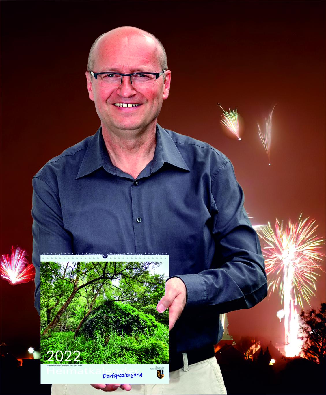 Ortsbürgermeister Matthias Mahl präsentiert den Heimatkalender 2022 vor dem Motiv des Monats Januar, dem Silversterfeuerwerk über Hütschenhausen.